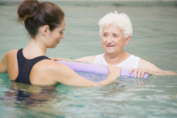 The caregiver teach the old woman how to swim